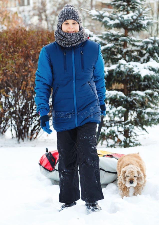 Зима, отдых и концепция развлечений милый молодой мальчик в играх синего пиджака со снегом, имеет потеху, улыбки Подросток идет с стоковая фотография rf