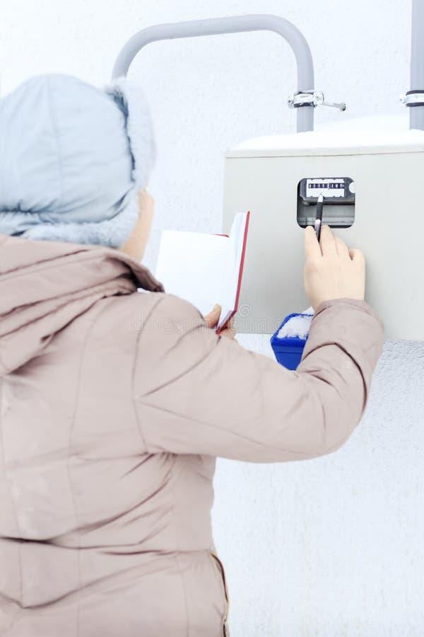 Зима, снег, холодный девушка, инженер, работник записывает чтения датчиков и манометров Они обнаружены местонахождение стоковое изображение
