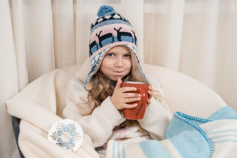 Зимнее время, маленькая девочка дома в кресле с большой чашкой горячего чая, в теплой связанной шляпе под шерстяным одеялом стоковое фото rf