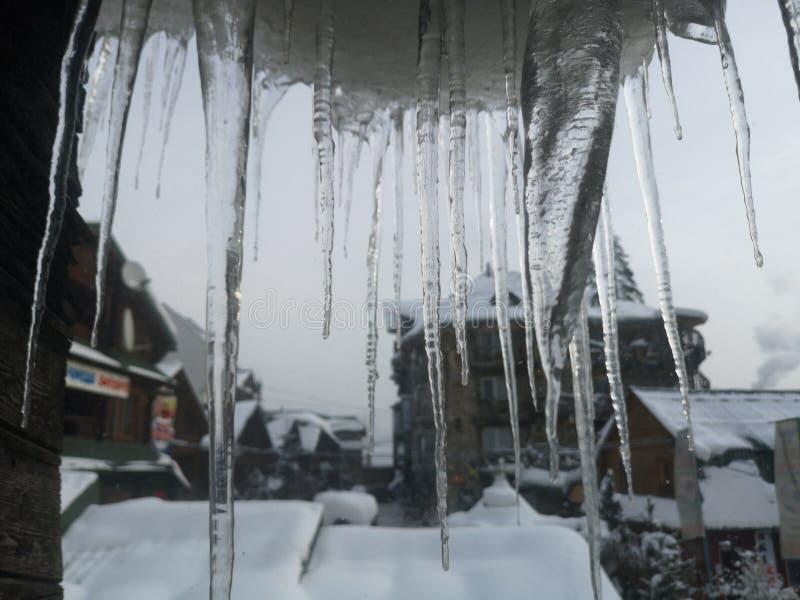 Зимние ледники на оконной раме с красивым видом на горный лес с горнолы стоковые изображения rf