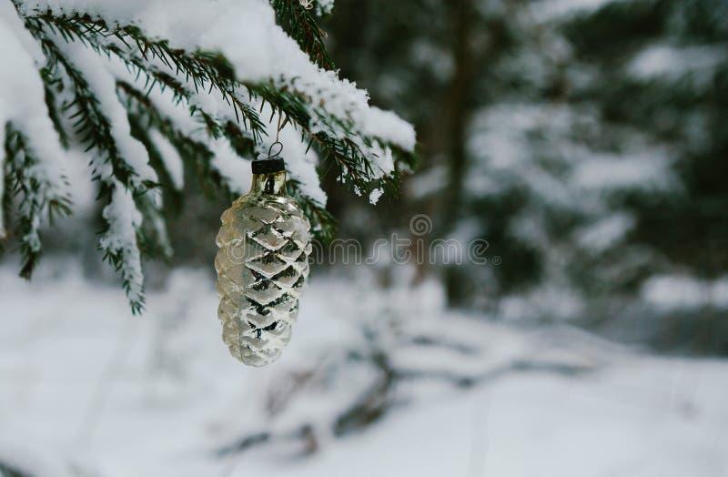 Зимние отдыхи и концепция украшения - шарик рождества на ветви ели покрытой со снегом стоковое изображение rf