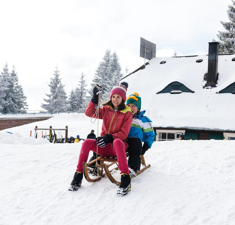 Зимний день с снегом и счастливые дети спуская sledding выплескивают стоковое изображение