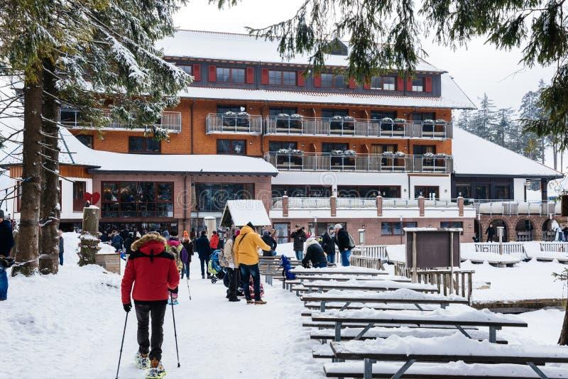 Зимний день с снегом при люди идя к озеру Mummelsee стоковое изображение