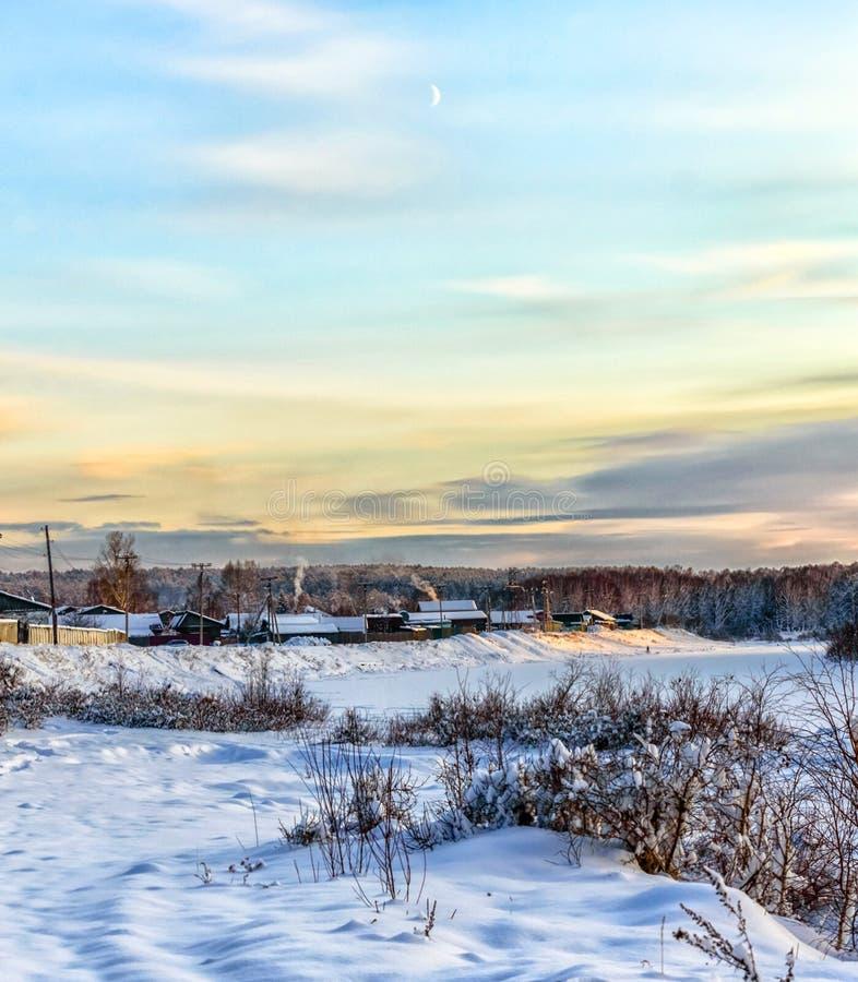 Зимний ландшафт Новая луна висела над деревней Холод Птицы нагреваются в домах Дым идет из труб. стоковое фото