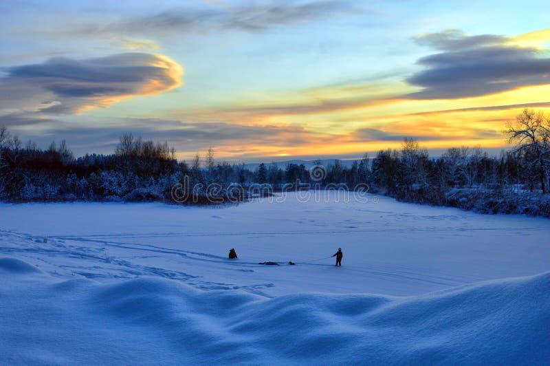 Зимний пейзаж Вечерние сумерки Дети играют на снегу Зимнее веселье стоковое фото rf