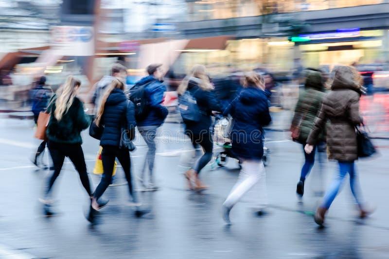 Зимняя сцена улицы в городе при люди пересекая улицу стоковое фото