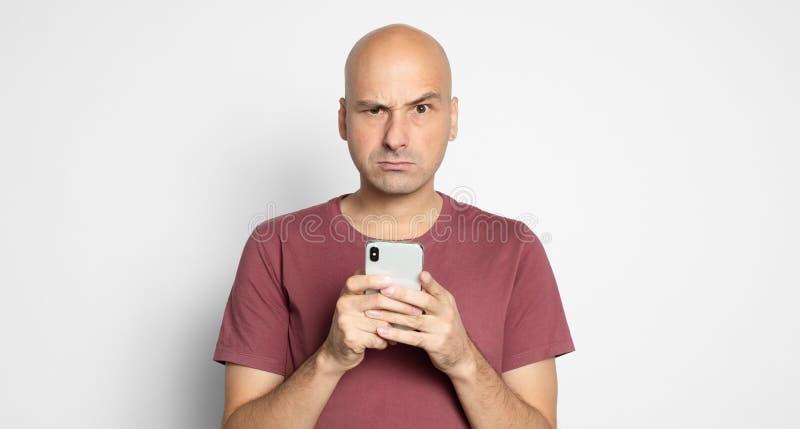 Злобый лысый человек держит смартфон. Изолировано стоковые фотографии rf