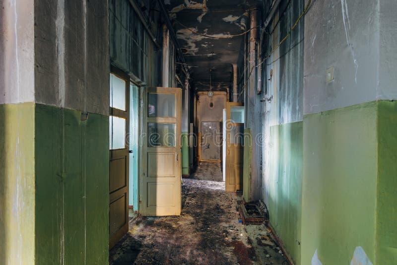 Зловещий и страшный коридор покинутой больницы после огня Потолок в черной саже стоковое фото rf
