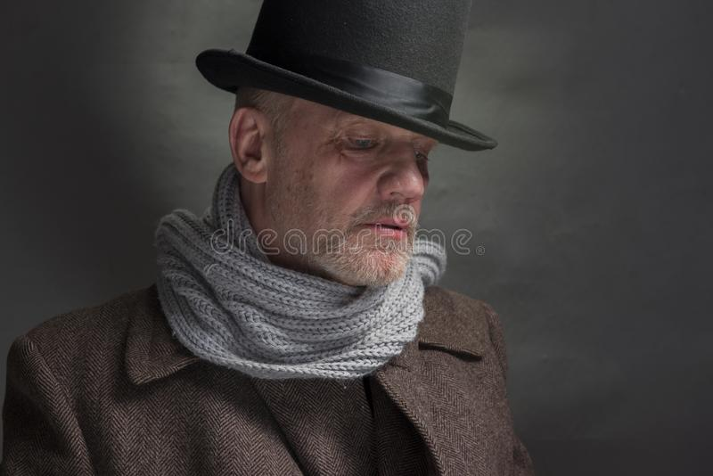 Зловещий человек нося верхнюю шляпу и серый шарф стоковое фото rf