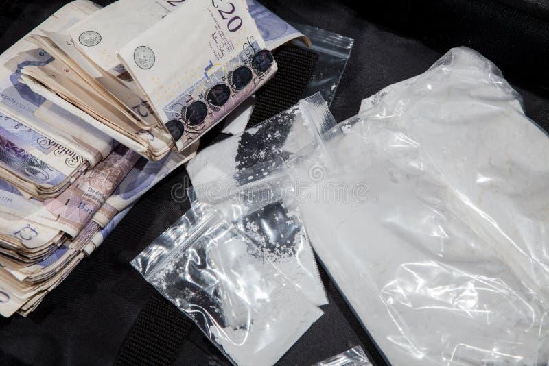 Злодеяние лекарства Великобритании Наличные деньги и кокаин Наличные деньги торговцев от продавать беду стоковые фотографии rf
