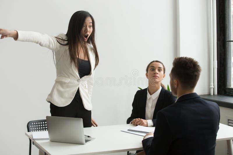 Злющая коммерсантка сердитая на бизнесмене говоря выйти mult стоковое фото rf
