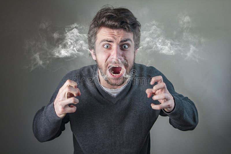 Злющий человек испаряясь с ражем стоковые фотографии rf