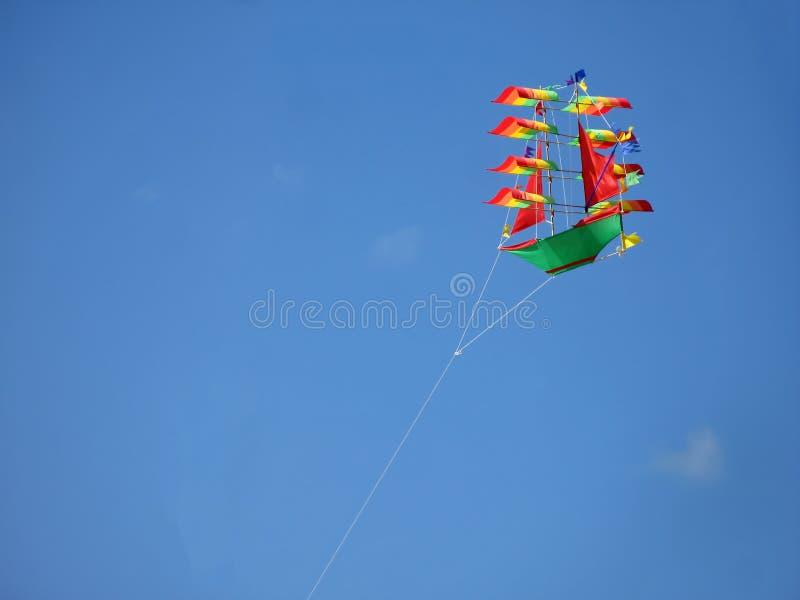 Змей в небе Покрасьте летание змея корабля в небе на яркий солнечный день стоковые фото