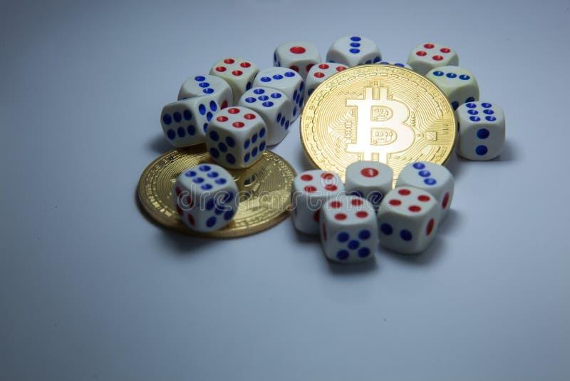 Знаки внимания cryptocurrency Bitcoin в центре dices на темной белой предпосылке Вклад, неопределенность валюты, риск и вознаграж стоковое фото rf