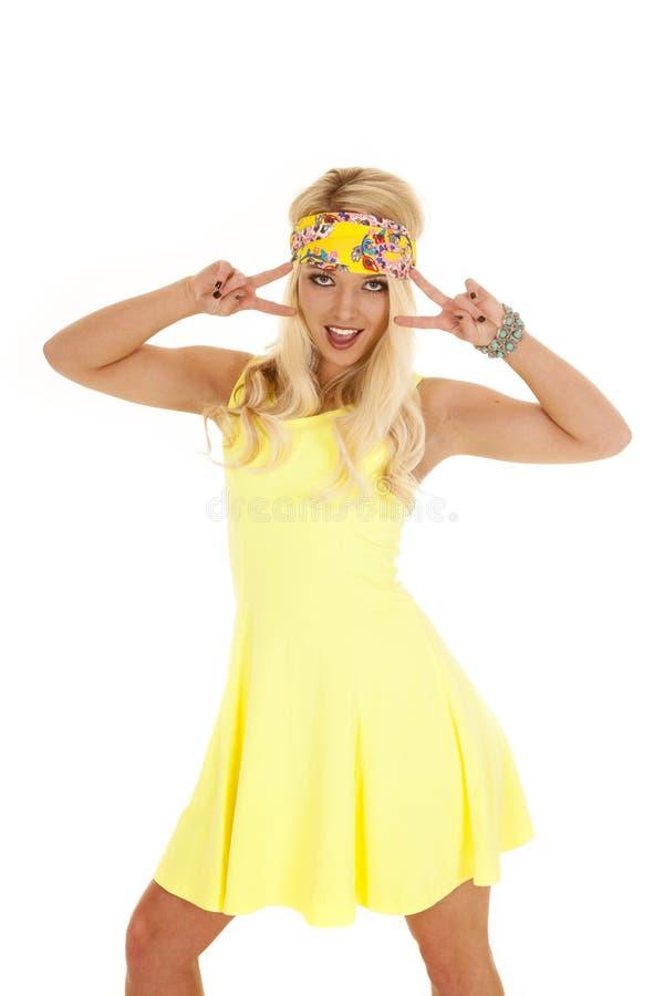 Знаки мира стойки 2 держателя платья желтого цвета женщины стоковое фото