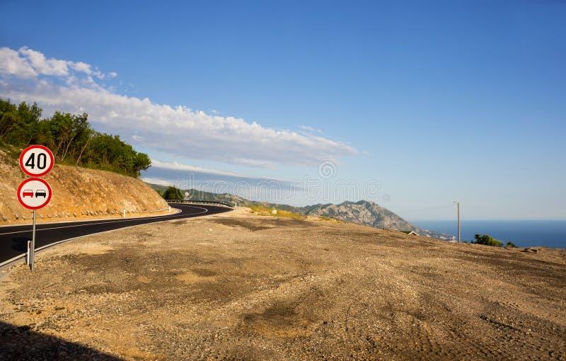 Знаки на повороте дороги в горах над морем стоковые изображения rf