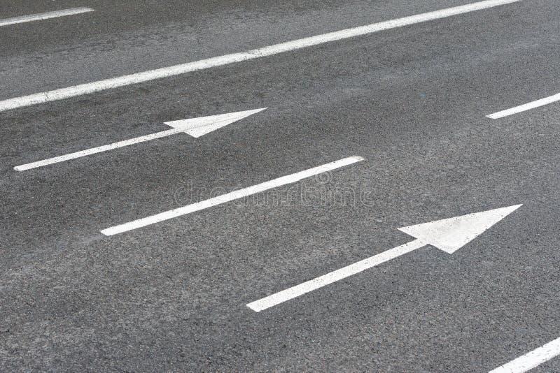 Знаки стрелок на городской дороге асфальта стоковые фото