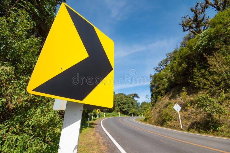 Знаки уличного движения говорят правильное направление кривой на шоссе горы, стоковые фотографии rf