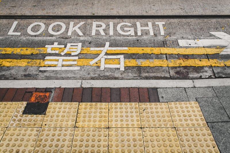Знак английским и китайским выглядеть правый на улице в Гонконге, советуя безопасности для пешеходов стоковое фото rf