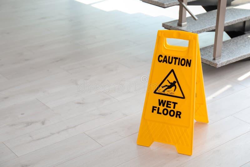 Знак безопасности с полом предосторежения фразы влажным около лестниц стоковые изображения rf