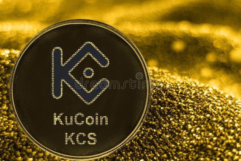 Знак внимания cryptocurrency KCS KUcoin монетки на золотой предпосылке стоковые фотографии rf