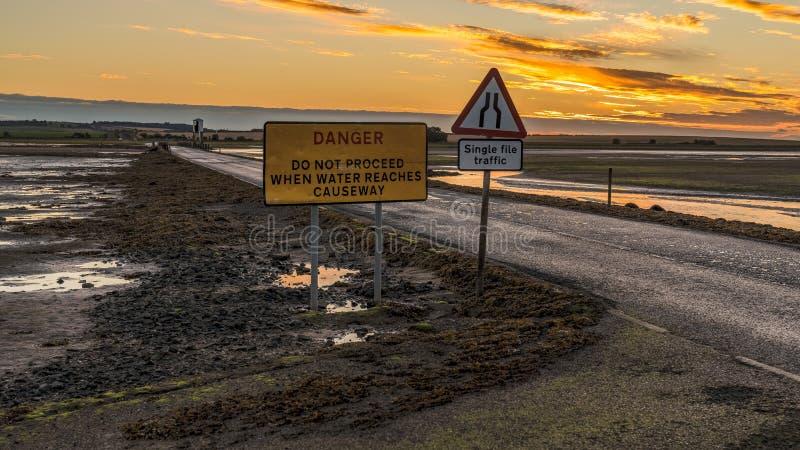 Знак: Движение отдельного файла, опасность не продолжает когда вода достигает мощеную дорожку стоковые фотографии rf