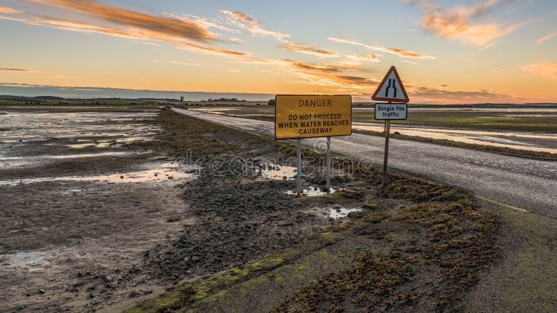 Знак: Движение отдельного файла, опасность не продолжает когда вода достигает мощеную дорожку стоковая фотография