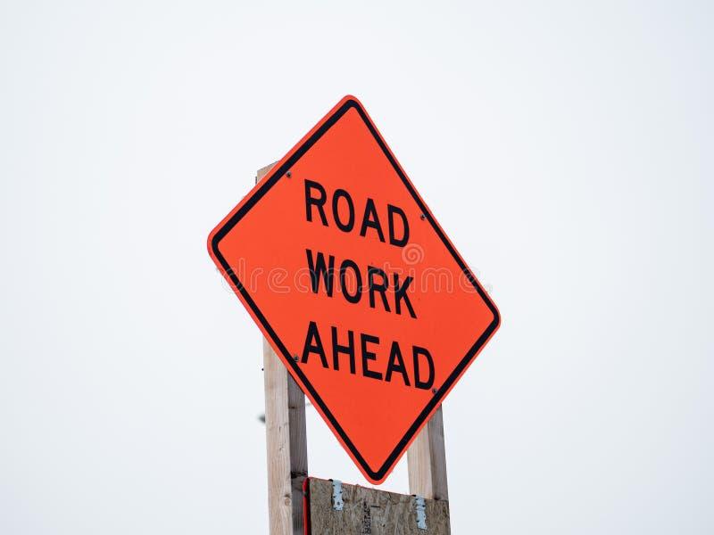 Знак дорожной работы вперед оранжевый вывешенный на деревянный столб на небе overcast стоковые фото