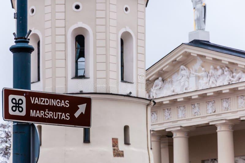 Знак информации со сценарным названием маршрута, колокольней и основной частью фасада базилики собора St Stanislaus и стоковая фотография rf