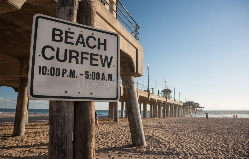 Знак комендантского часа пляжа под пристанью стоковые изображения rf