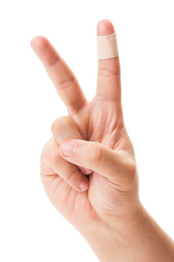 Знак мира с залатанным пальцем стоковые фотографии rf