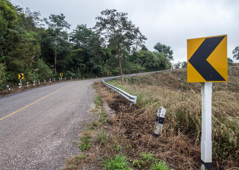 Знак направления дороги асфальта кривой стоковое фото
