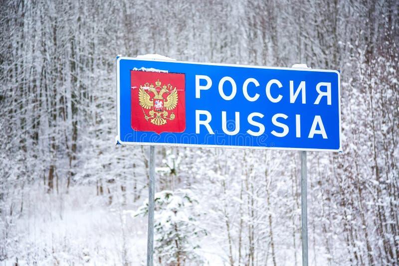 Знак национальной границы Российской Федерации во время зимы - дорожного знака Беларуси на границе с областью России Пскова стоковые фотографии rf