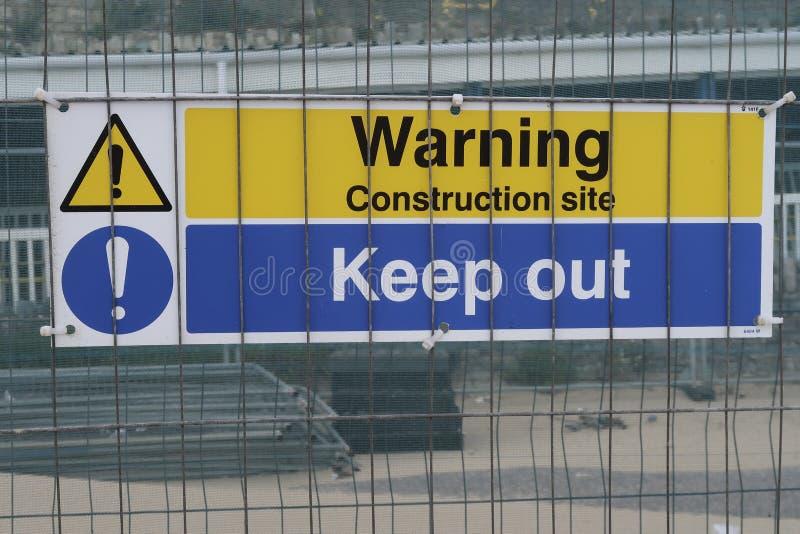 Знак на строя районе с строительной площадкой текста предупреждающей держит вне стоковое фото