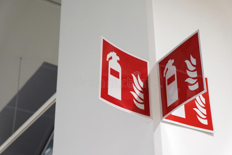 Знак огнетушителя на белой стене стоковые изображения rf