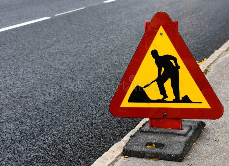 Знак дорожной работы сбоку дороги стоковое изображение