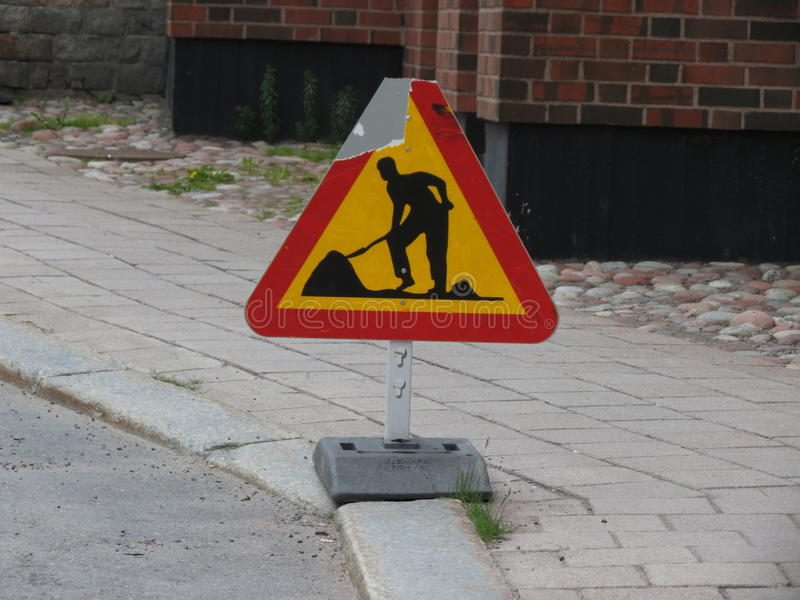 Знак дорожных работ тяжело повреждает стоковое фото rf