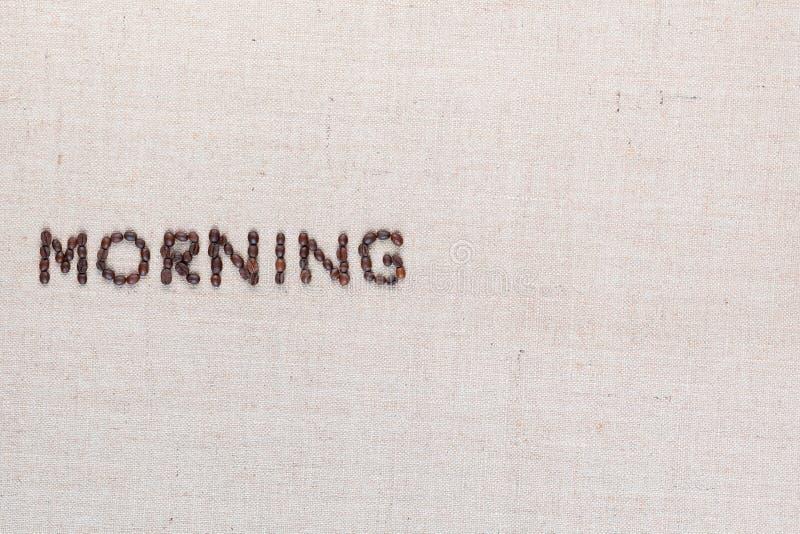 Знак письма утра от кофейных зерен изолированных на текстуре linea, выровнял среднюю левую сторону стоковое изображение