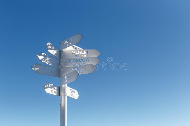 Знак показывая направления и расстояния к различным городам мира Направление городов на предпосылке голубого s стоковое изображение rf