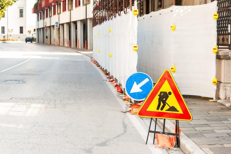 Знак работы в процессе на дороге стоковое фото
