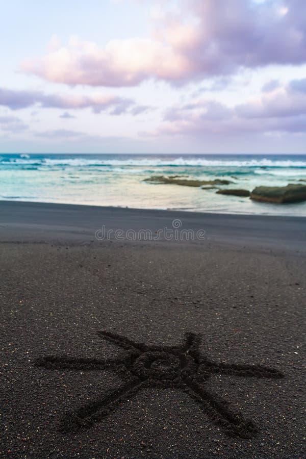 Знак Солнця нарисованный на отработанной формовочной смеси пляжа стоковые изображения