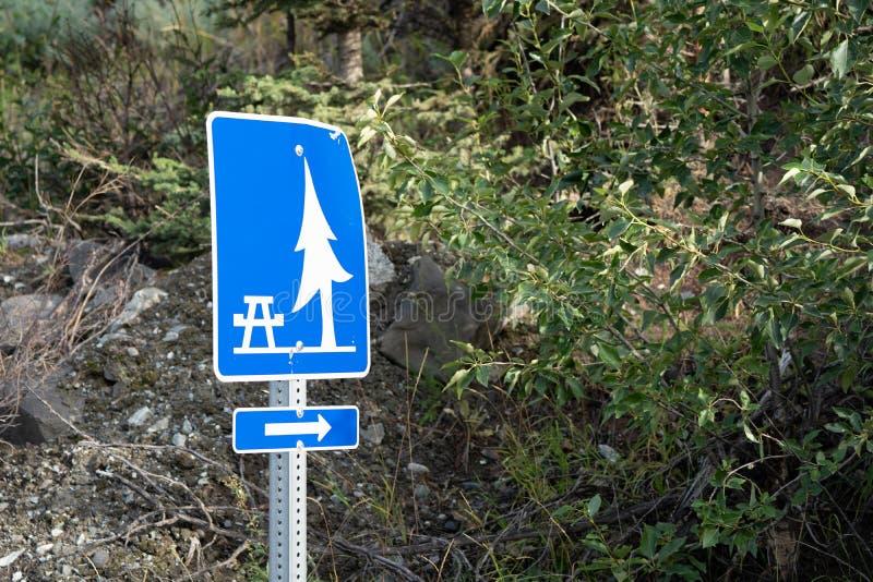 Знак сразу к обозначенной зоне пикника с таблицами и тенью стоковые изображения rf