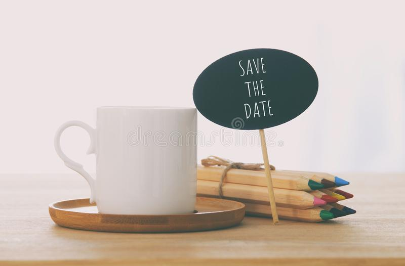 знак с текстом: СОХРАНЬТЕ ДАТУ рядом с чашкой кофе над деревянным столом стоковое изображение