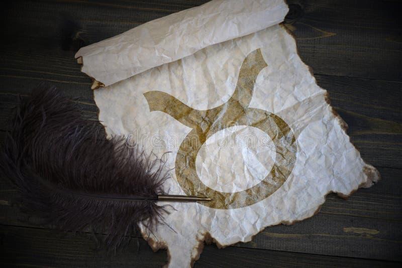 Знак Тавра зодиака на винтажной бумаге с старой ручкой на деревянном столе стоковая фотография