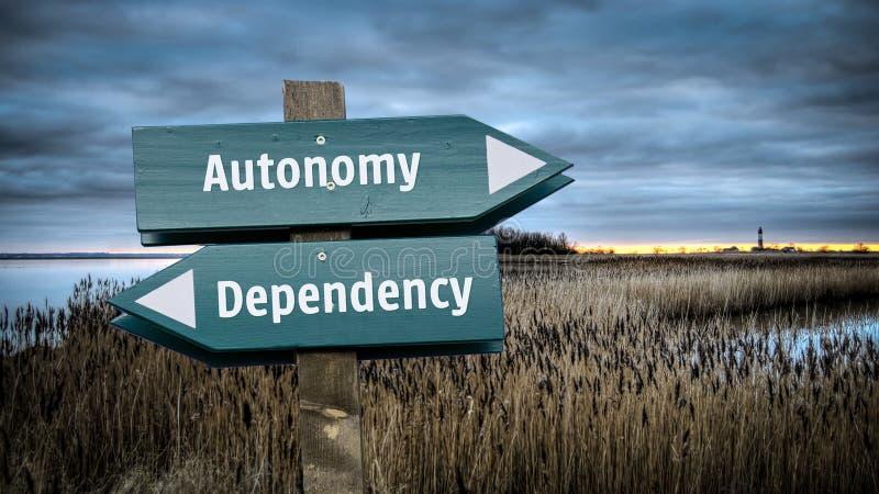 Знак улицы к автономии против зависимости стоковое изображение