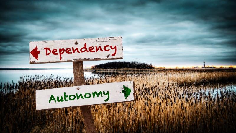 Знак улицы к автономии против зависимости стоковые фотографии rf