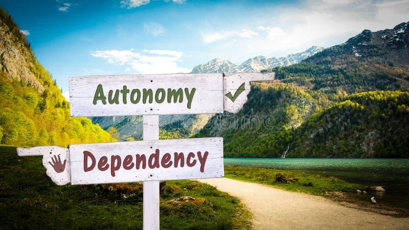 Знак улицы к автономии против зависимости стоковые изображения