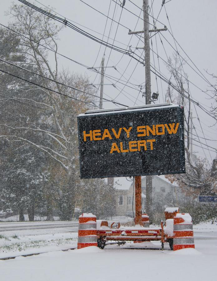 Знак электрического дорожного движения мобильный стороной дороги покрытой снегом с предупреждением снега понижаясь сигнала тревог стоковая фотография