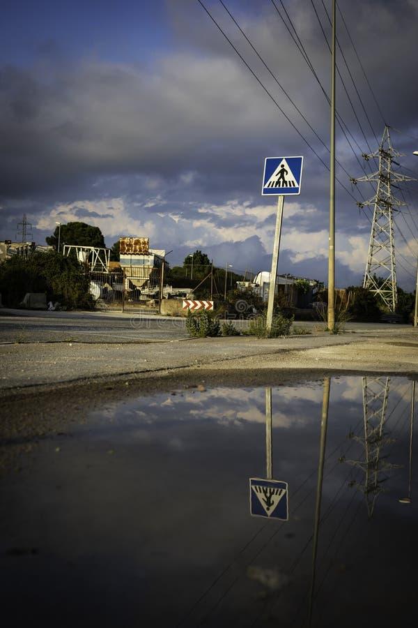 Знак Crosswalk с отражением пруда на пасмурный день с темно-синим небом стоковые фотографии rf