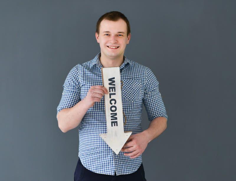 Знамя доски гостеприимсва удерживания молодого человека, стоя на темной предпосылке стоковое изображение